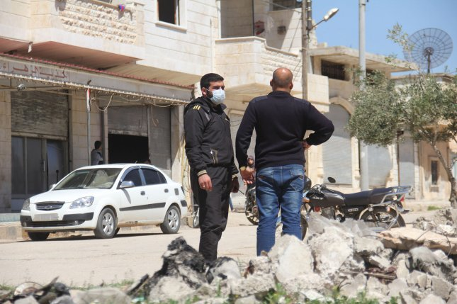 Syrian men collect samples from the site of a suspected toxic gas attack in Khan Sheikhun, in Syria's northwestern Idlib Province, on Wednesday. Photo by Omar Haj Kadour/UPI