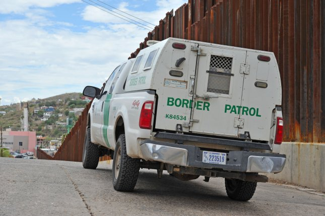A U.S. Border Patrol truck is seen next to the barrier between the United States and Mexico near Nogales, Arizona. A new report by the ACLU says little has been done to stop abuse of children in federal immigration custody. File Photo by Art Foxall/UPI