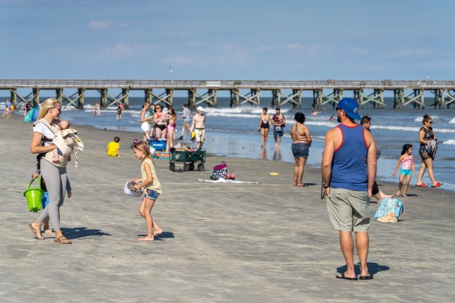 People hit the beach in Isle of Palms, S.C., on Wednesday after the the city relaxed restrictions.  Photo by Richard Ellis/UPI