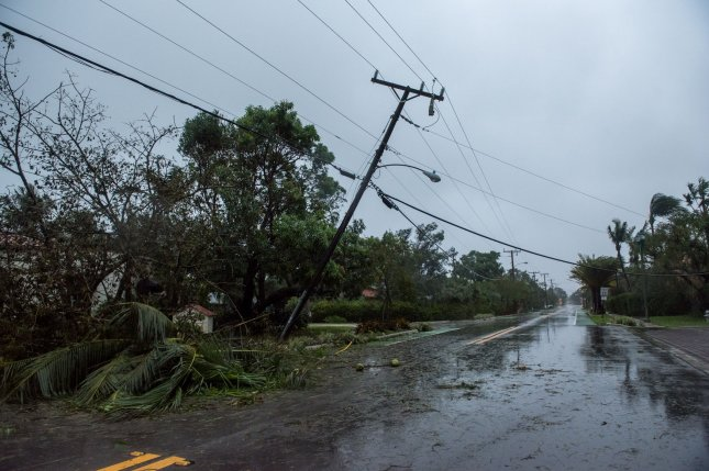 A power pole leans into a debris-covered street in Delray Beach, Fla., after Hurricane Irma passed through on September 10, 2017. The storm caused nearly $1.4 billion in power restoration costs. File Photo by Ken Cedeno/UPI