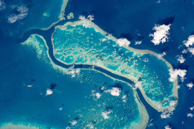 An astronaut aboard the International Space Station captured a view of three reefs forming Australia's Great Barrier Reef. A study revealed on Friday of fish species caught in a 2016 heatwave at the Reef indicates that the species adapted at different rates. Photo courtesy of NASA/UPI
