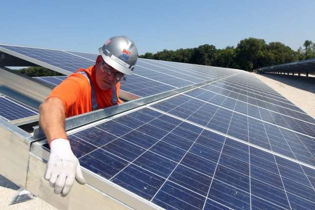 Keith Plume of PayneCrest Electric Company checks that solar panels are lined up correctly at the Ameren O'Fallon Renewable Energy Center in O'Fallon, Missouri. File Photo by Bill Greenblatt/UPI