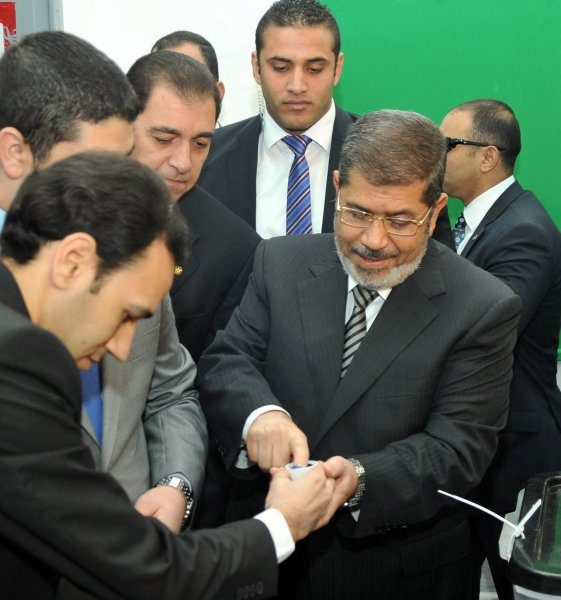 Egyptian President Mohamed Morsi dips his finger in ink after voting during the referendum for a new constitution, at a polling station in Cairo, Egypt, 15 December 2012. Polling places opened on 15 December in 10 of Egypt's provinces in the first round of a referendum on a draft constitution that provoked demonstrations by pro- and anti-government protesters. UPI/POOL