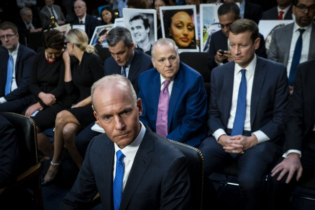 Relatives hold photographs of those who died in two crashes of Boeing 737 Max aircraft as CEO Dennis Muilenburg testifies October 29 at a safety hearing on Capitol Hill. File Photo by Pete Marovich/UPI