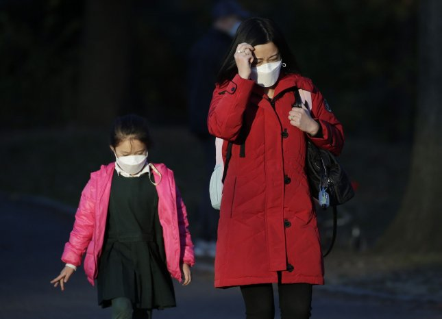 A woman and child wear face masks to protect from and prevent the spread of Coronavirus in Central Park in New York City on November 20. Photo by John Angelillo/UPI