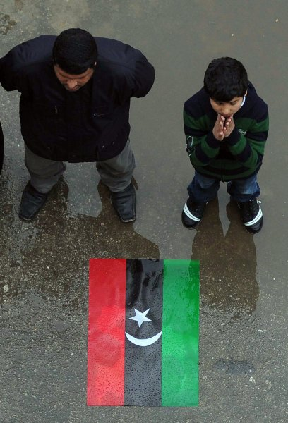 Protesters stand in front of the old national flag as they shout slogans against Libyan leader Moammar Gadhafi near the port of Benghazi, Libya along the Mediterranean coast on March 6, 2011. Loyal and rebel forces continue to battle for control of the country. UPI/Mohamaad Hosam