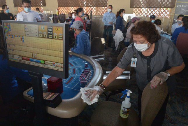 A masked casino worker sanitizes a card table at the Gardens Casino in Hawaiian Gardens, Calif., on Wednesday. Partitions and seats are sanitized each time a customer leaves to prevent the spread of COVID-19. Photo by Jim Ruymen/UPI