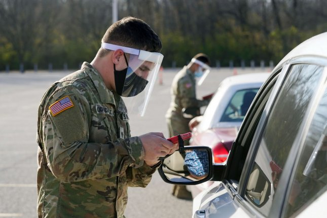 Members of the Missouri National Guard check paperwork on Thursday for people waiting for drive-through COVID-19 testing at the Family Arena in St. Charles, Mo. The National Guard have been testing nearly 400 people per day. Photo by Bill Greenblatt/UPI