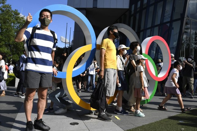 Visitors pose by the Olympic rings outside Olympic Stadium in Tokyo, Japan, last Friday. Photo by Mike Theiler/UPI
