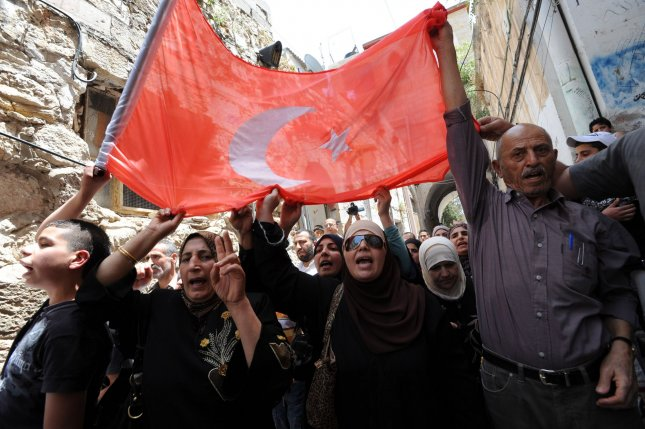 Palestinians chant while carrying a Turkish flag in the Old City of Jerusalem. UPI/Debbie Hill