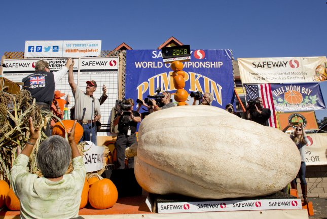 John Hawkley (2nd- L) celebrates next to his 2058 pound winning entry at the 41st annual Half Moon Bay Pumpkin Weigh-off in Half Moon Bay, California on October 13, 2014. Hawkley will get a check for $13,348, that's $6 per pound, for his pumpkin that weighed-in at 2,058 pounds and $1000 for breaking the state record. UPI/Mohammad Kheirkhah