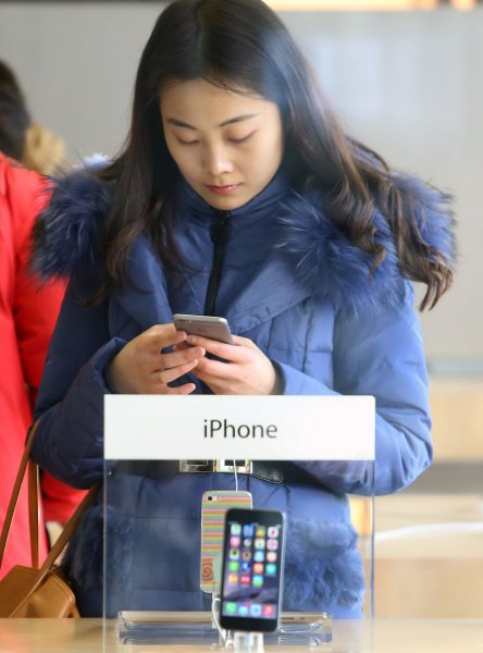 A Chinese woman examines an iPhone 6 at Apple's flagship store in Beijing on January 4, 2015. Some sperm banks in the country are using the upcoming release of the iPhone 6s to draw in donors. Photo by Stephen Shaver/UPI