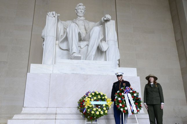 Acting Superintendent National Mall and Memorial Parks Karen Cururullo (R) stands at attention after presenting a wreath on February 12, 2018. On February 12, 1914, a dedication ceremony was held and the first stone of the Lincoln Memorial was laid. It took eight years to complete the monument. Photo by Mike Theiler/UPI