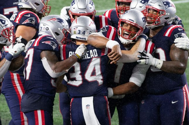 New England Patriots quarterback Cam Newton (1) hugs running back Rex Burkhead (34) after Burkhead caught a touchdown pass on a trick play to give the Patriots the lead in a Sunday Night Football win over the Baltimore Ravens on Sunday in Foxborough, Mass. Photo by Matthew Healey/UPI