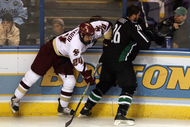 North Dakota Sioux Kyle Radke (R) loses his helmet after being checked into the boards by Boston College Eagles Matt Lombardi during the first period of their semi-final game of the 2007 Mens NCAA Frozen Four at the Scottrade Center in St. Louis on April 5, 2007. (UPI Photo/Bill Greenblatt)