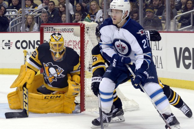 Winnipeg Jets left wing Nikolaj Ehlers (27) plays the puck from behind the net as Pittsburgh Penguins goalie Marc-Andre Fleury (29) watches from the goal in the first period of the Penguins 4-1 win at the Consol Energy Center in Pittsburgh on February 27, 2016. Photo by Archie Carpenter/UPI