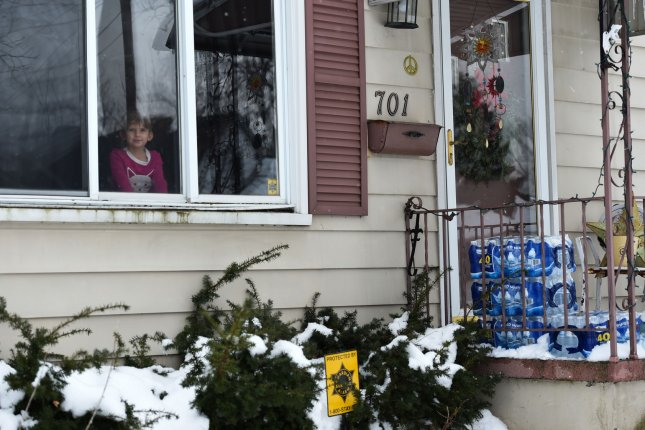 A child in Flint, Mich. -- where lead contaminated the drinking water -- watches as bottled water is delivered to their home. Lead exposure in childhood can impact brain development well into adulthood, a new study has found. Photo by Molly Riley/UPI