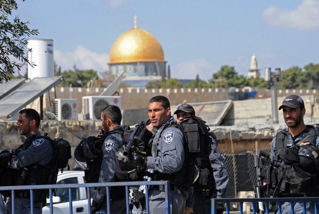 Israeli riot police guard Palestinians, not seen, praying on the street in the East Jerusalem neighborhood of Ras al-Amud after being refused entry to travel to the Old City of Jerusalem and the Al-Aqsa Mosque compound, on October 17, 2014. (UPI/Debbie Hill)