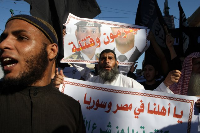 A Palestinian Salafist at a rally in Rafa in southern Gaza on August 22, 2013. Behind him is a poster showing Syrian President Bashar al-Assad (R) and Egypt's army chief General Abdel Fattah al-Sisi, now president of Egypt, with the Arabic words reading criminals and murderers. Several experts on the Middle East have suggested that Quietist Salafists, who shun involvement in politics, could mount an effective ideological and religious opposition to jihadists. File Photo by Ismael Mohamad/UPI