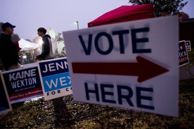 Volunteers wait outside a polling location in Leesbugh, Va., on Tuesday. Photo by Kevin Dietsch/UPI