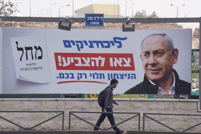A man walks past a campaign poster for Israeli Prime Minister Benjamin Netanyahu on February 24. A court on Tuesday declined to delay the start of Netanyahu's corruption trial next week. Photo by Debbie Hill/UPI