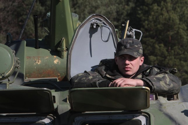 A Ukrainian soldier sits in a tank during a military exercise near Goncharovsk village of the Chernigov area in Ukraine on March 14, 2014 as Russian troops gathered near the Ukraine border for exercises during the standoff over Crimea. (UPI/Sergey Starostenko)