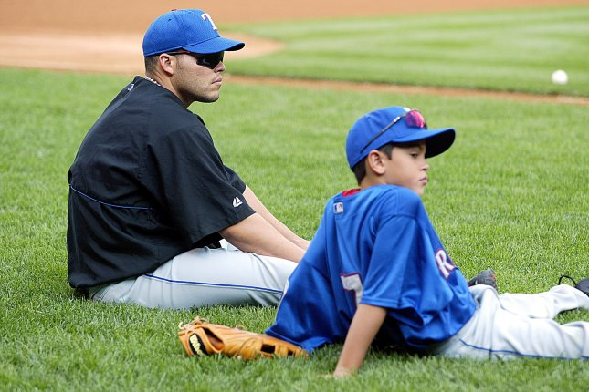 Former Texas Rangers catcher Ivan Rodriguez and his son watch batting practice prior to a New York Yankees and Texas Rangers game in 2002 at Yankee Stadium in New York. File photo by Laura Cavanaugh/UPI