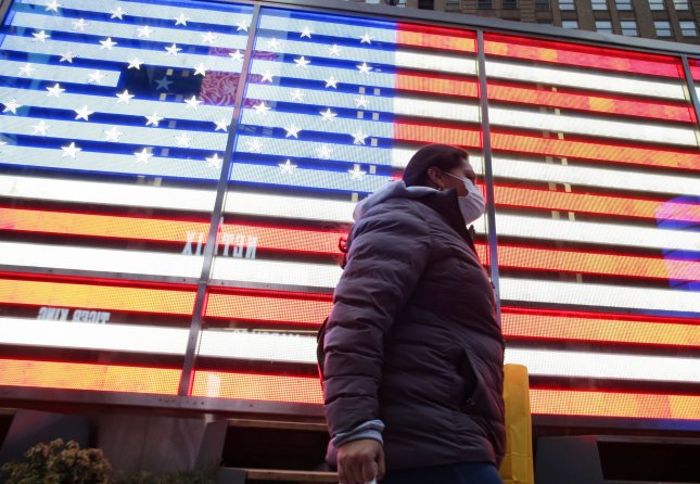 A woman walks past a giant American Flag wearing a face mask in Times Square in New York City on Thursday. Photo by John Angelillo/UPI