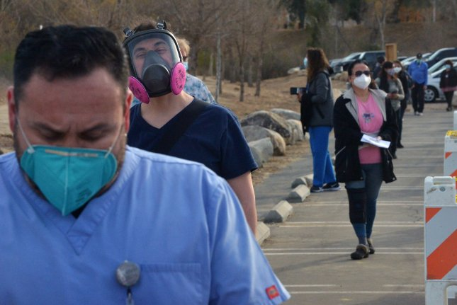 Healthcare workers, who are at greater risk for COVID-19 in the community than they are when treating patients, are pictured standing in line to get vaccinated against the coronavirus. File photo by Jim Ruymen/UPI