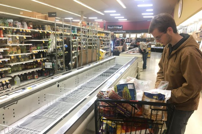 A shopper looks for food near an empty refrigerated section at a grocery store in San Francisco, Calif., on March 16. Many stores temporarily ran out of supplies due to the coronavirus health crisis. File Photo by Terry Schmitt/UPI