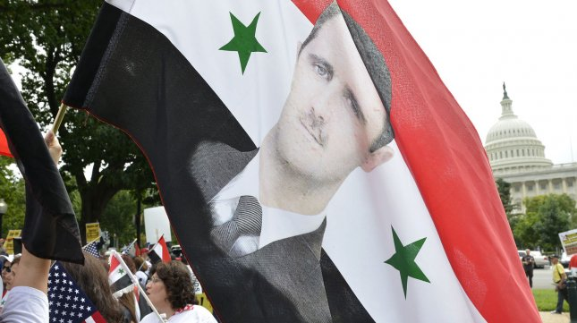 Pro-Syrian regime demonstrators hold a flag with the image of Syrian President Bashar Assad during a rally on Capitol Hill, September 9, 2013, in Washington, DC. President Barack Obama is expected to address the nation on a possible US military strike against Syria for chemical weapons attacks on civilians as Congress weighs a war resolution. UPI/Mike Theiler