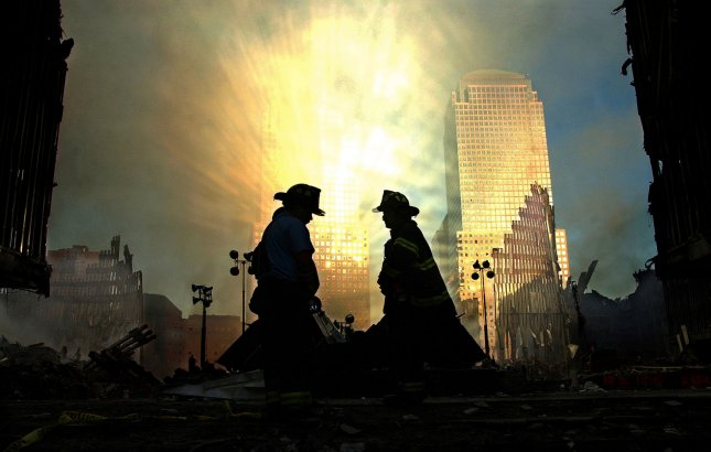 Rays of light burst off a building at One Liberty Plaza to silhouette two firefighters who are surveying Ground Zero at dawn on September 15, 2001 in New York City. UPI/Chris Corder