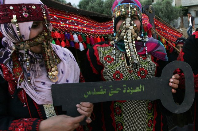 Palestinian women wearing traditional Arabic headdress (Burqa) hold a key with the Arabic writing, we will return for sure, during a rally to mark the 64th anniversary of Nakba, Arabic for Catastrophe, the term used to mark the events leading to Israel's founding in 1948, in Nusseirat refugee camp, southern Gaza on May 15, 2012. UPI/Ismael Mohamad