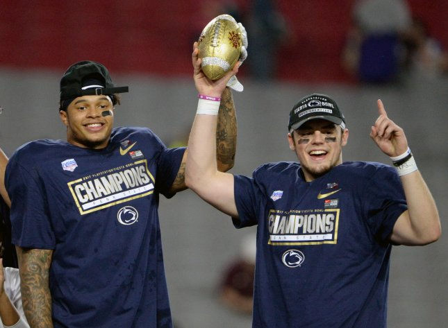Penn State's Marcus Allen (L) and Trace McSorley hold up the Fiesta Bowl Trophy after defeating the Washington Huskies' 35-28 on Saturday. Photo by Art Foxall/UPI