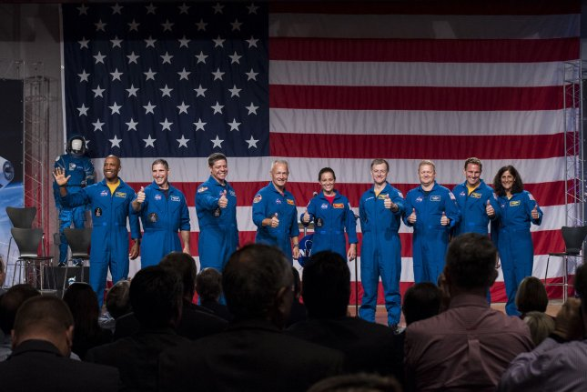 The first U.S. astronauts who will fly on American-made, commercial spacecraft to and from the International Space Station, wave after being announced Friday at NASA's Johnson Space Center in Houston, Texas. From left to right: Victor Glover, Mike Hopkins, Bob Behnken, Doug Hurley, Nicole Aunapu Mann, Chris Ferguson, Eric Boe, Josh Cassada, and Suni Williams. NASA Photo by Bill Ingalls/UPI