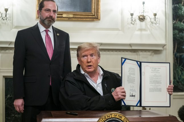 President Donald Trump signs an $8.3 billion coronavirus supplemental funding bill Friday, alongside Secretary of Health and Human Services Alex Azar, in the Diplomatic Room of the White House. Photo by Jim Lo Scalzo/UPI