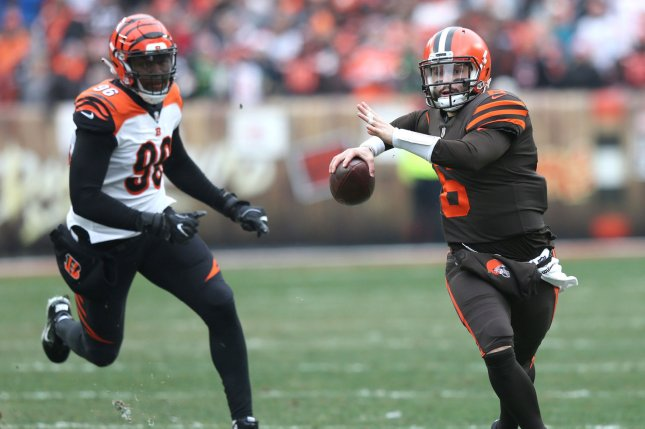Cleveland Browns quarterback Baker Mayfield makes a throw as he runs from Cincinnati Bengals defensive lineman Carlos Dunlap in the first half on Sunday at FirstEnergy Stadium in Cleveland. Photo by Aaron Josefczyk/UPI