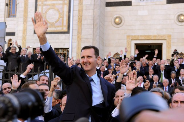 Syrian President Bashar al-Assad waves to supporters in the street after addressing parliament on March 30, 2011 in Damascus, Syria. Al-Assad ordered a committee to conduct an investigation into the deaths of protesters and also to study the lifting of emergency laws. UPI