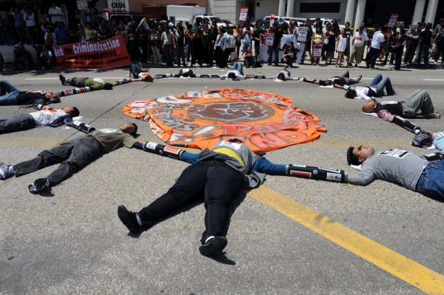 Protesters lie on a street with their hands linked together during a demonstration organized by We Are All Arizona against Arizona's new law SB 1070, near the U.S. Immigration and Customs Enforcement offices in downtown Los Angeles May 6, 2010. The law requires state and local police to determine people's immigration status if there is reasonable suspicion they are in the United States illegally. UPI/Jim Ruymen