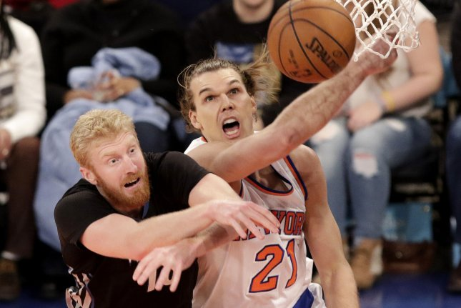 Minnesota Timberwolves Chase Budinger and New York Knicks Lou Amundsen reach for a loose basketball in the first half at Madison Square Garden in New York City on March 19, 2015. Photo by John Angelillo/UPI