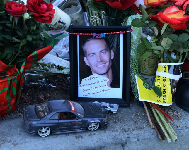 Fans gather at a makeshift memorial to pay respects at the site of the fiery car accident in which actor Paul Walker was killed in Santa Clarita, California, on December 4, 2013. Fans and fellow actors mourned the death of Paul Walker, who died in a fiery car crash on Saturday, Nov. 30, 2013. File Photo by Jim Ruymen/UPI