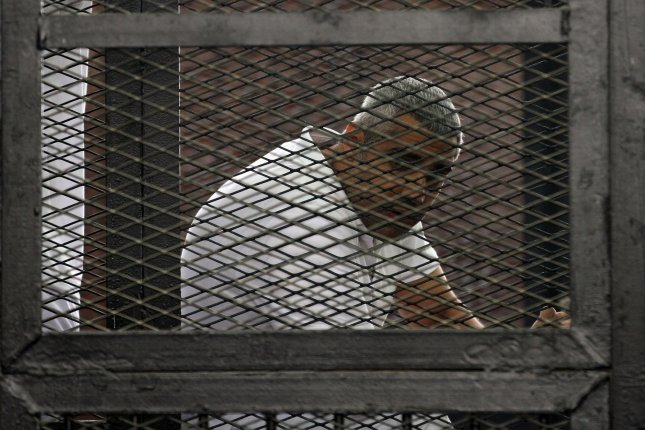 Journalist Mohamed Fahmy stand behind caged bars a court in Cairo, Egypt on June 23, 2014. Photo courtesy of UPI/Karem Ahmed