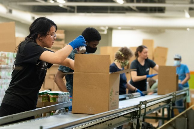 A worker packs a box of food to be distributed to needy in Washington, D.C., on April 9, as a result of the coronavirus pandemic. File Photo by Kevin Dietsch/UPI