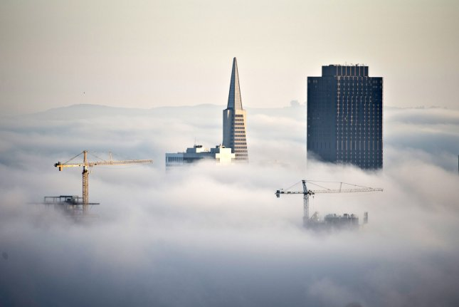 Construction cranes join the Transamerica Pyramid and 555 California Street (R) jutting through the fog at sunrise in San Francisco on October 20, 2013. San Francisco is seeing a boom in new housing and commercial construction alter the skyline. Construction added 20,000 jobs in September, while wholesale trades gained 16,000. UPI/Terry Schmitt