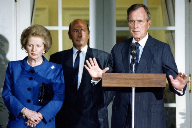 U.S. President George Bush (R) gestures to reporters as he comments on the Iraq-Kuwait crisis in the Rose Garden of the White House on August 6, 1990. At left is British Prime Minister Margaret Thatcher and NATO Secretary-General Manfred Woerner. File Photo by Martin Jeong/UPI
