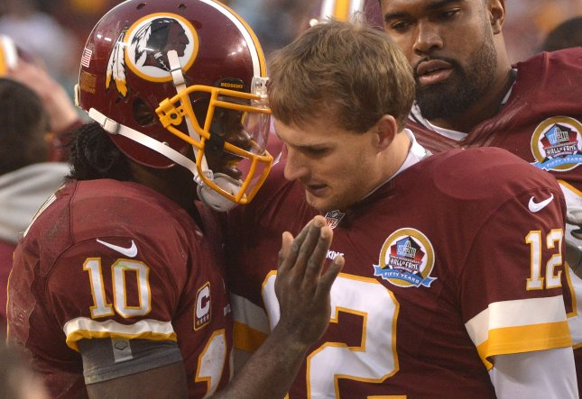 Washington Redskins quarterback Robert Griffin III (10) speaks with backup quarterback Kirk Cousins in a game Dec. 9, 2012, game. Cousins in Wednesday was named the starting Washington quarterback with Griffin to be listed as inactive for Sunday's game. UPI/Kevin Dietsch