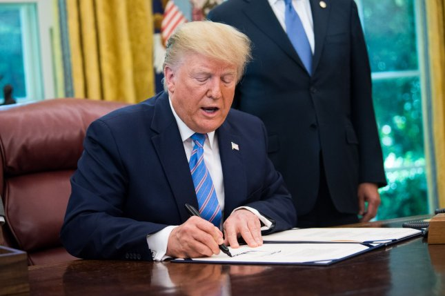 President Donald Trump signs a bill for border funding in the Oval Office at the White House on Monday. Photo by Kevin Dietsch/UPI