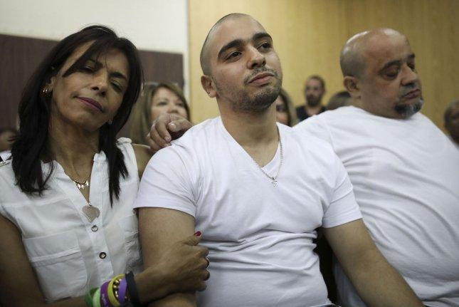 Israeli soldier Elor Azaria, flanked by his parents, sits inside a Israeli military court in Tel Aviv, Israel on July 30. Azaria's prison term has been reduced by four months. Pool File Photo by Dan Balilty/UPI