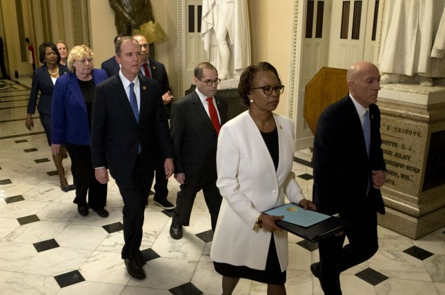Clerk of the U.S. House of Representatives Cheryl Johnson and Sergeant at Arms of the House of Representatives Paul Irving, followed by impeachment managers, transfer the articles of impeachment from the House to the Senate. Photo by Kevin Dietsch/UPI