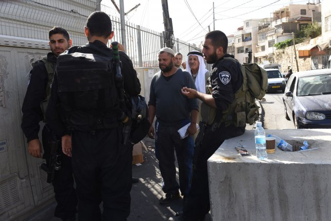 Israeli police check Palestinians identity cards next to newly installed concrete blocks on a main street in Ras al-Amud in east Jerusalem, October 15, 2015. Israel erected concrete blocks at the entrance to Palestinian villages as part of an intense effort to stop a wave of terror attacks in Jerusalem. Photo by Debbie Hill/ UPI